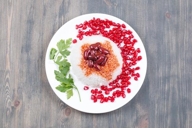 Plaat van gestoomde rijst met granaatappelpitjes op houten oppervlak