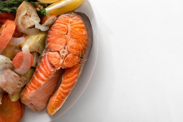 Plaat van gezonde voeding gebakken vis, zalm, salade op een witte plaat. op een witte marmeren achtergrond.