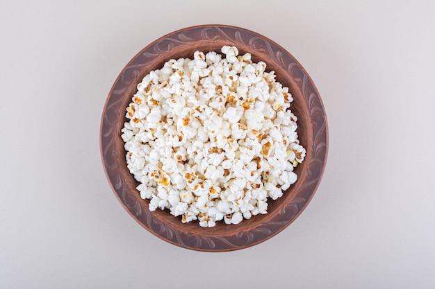 Plaat van gezouten popcorn voor filmavond op witte achtergrond. hoge kwaliteit foto