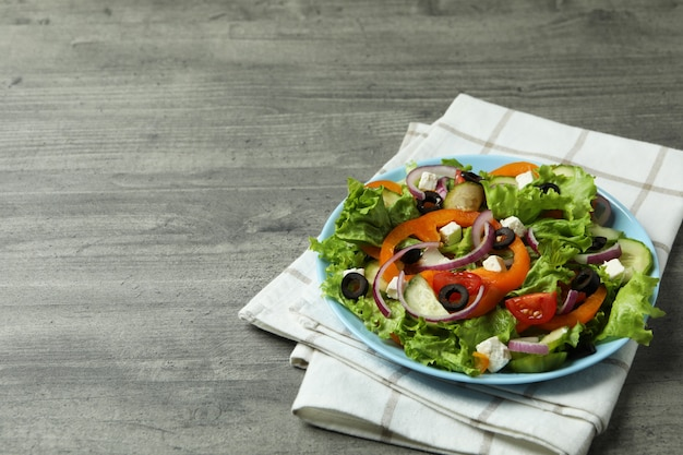 Plaat van griekse salade en keukenhanddoek op geweven grijs