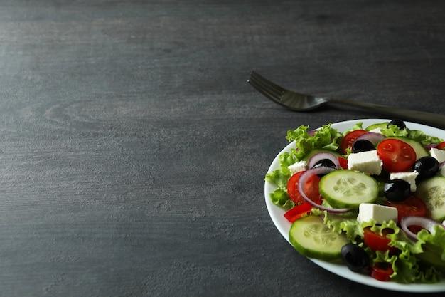 Plaat van griekse salade en vork op donkere houten