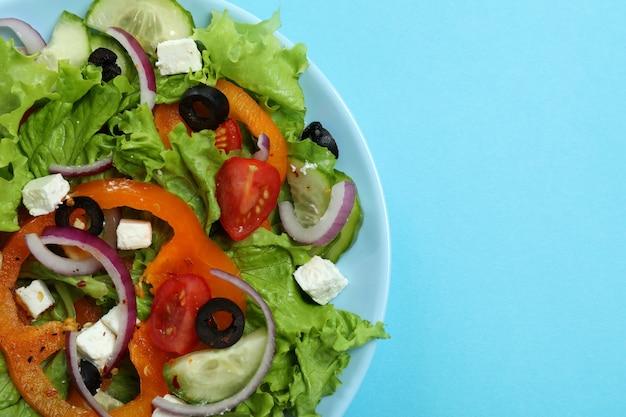 Plaat van griekse salade op blauwe ondergrond, close-up