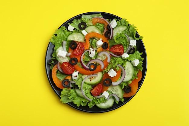 Plaat van griekse salade op geel