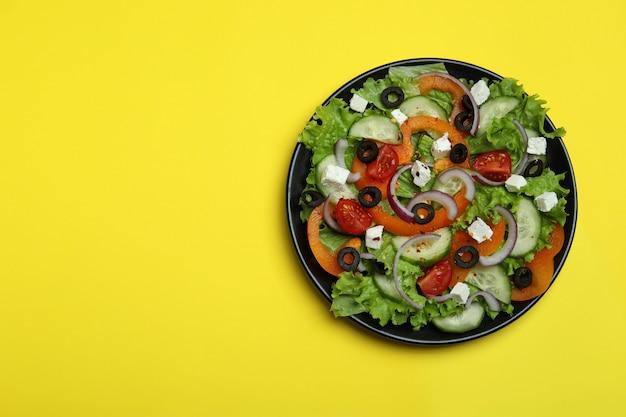 Plaat van griekse salade op gele ondergrond