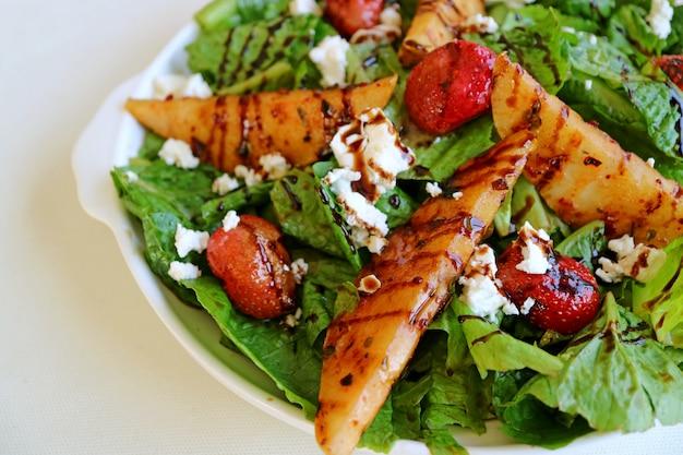 Plaat van groene salade met geroosterde peren en verse aardbeien