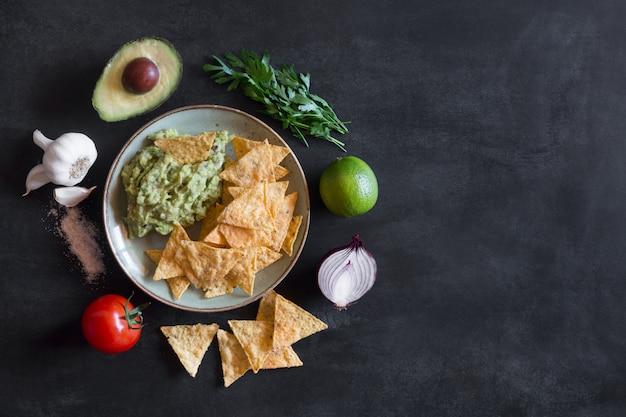 Plaat van guacamole met tortillachips en ingrediënten