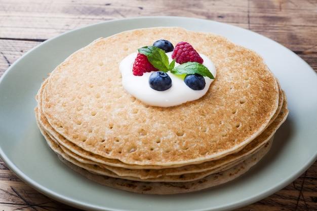Plaat van heerlijke dunne pannenkoeken met bessen op houten tafel