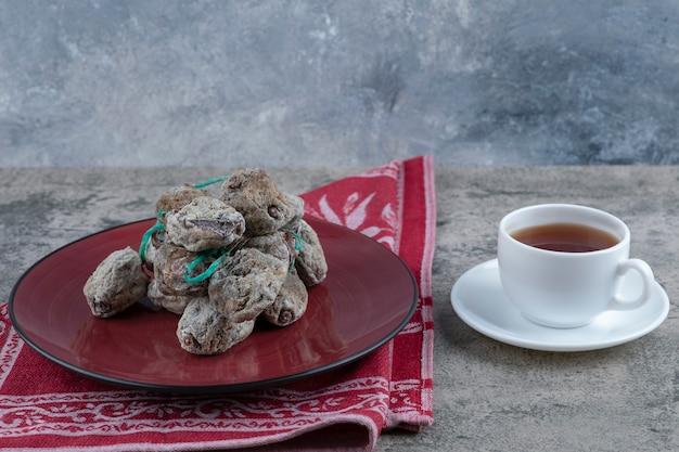 Plaat van heerlijke gedroogde dadelpruimvruchten met thee die op een steenlijst wordt geplaatst.