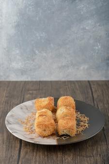 Plaat van heerlijke nest gebakjes geplaatst op houten tafel.