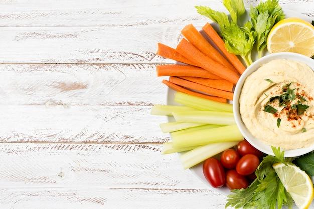 Plaat van hummus en assortiment van groenten met kopie ruimte