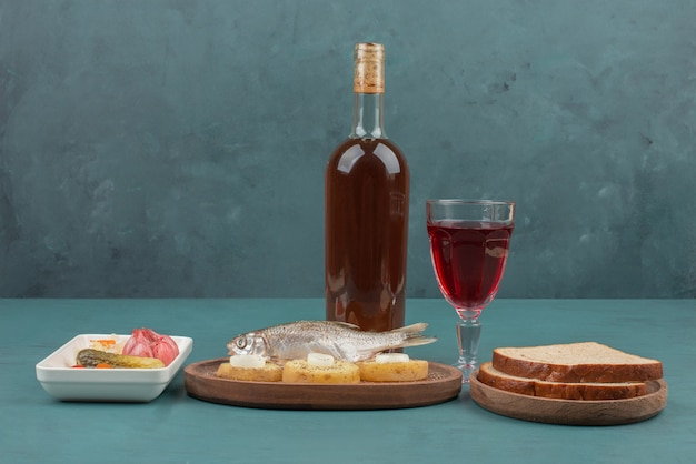 Plaat van ingemaakte groenten, vis, sneetjes brood en rode wijn op blauwe lijst.