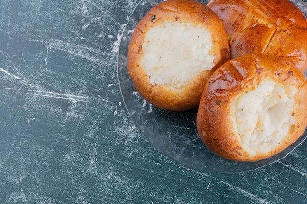 Plaat van kaasbroodjes op marmeren tafel.