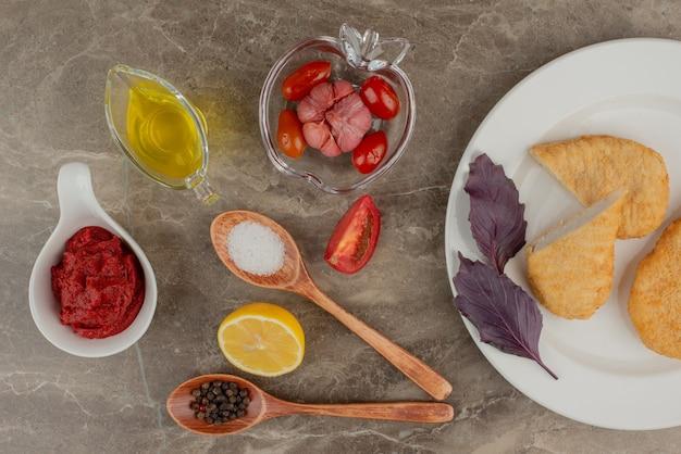 Plaat van kipnuggets en olie, lepels zout en peper.