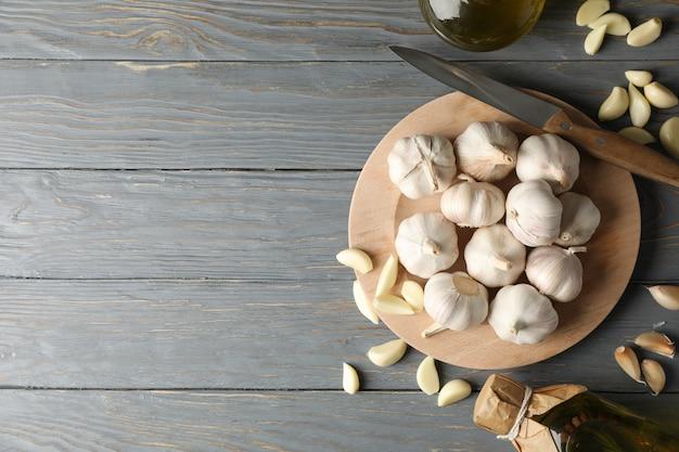 Plaat van knoflook bollen, plakjes, olie op grijze houten