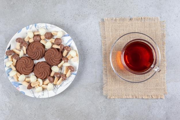 Plaat van koekjes met chocoladepaddestoelen naast een kopje thee op marmeren achtergrond. hoge kwaliteit foto