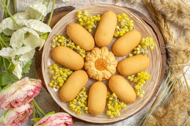 Plaat van koekjes op houten schotel en bloemen eromheen op marmeren grond