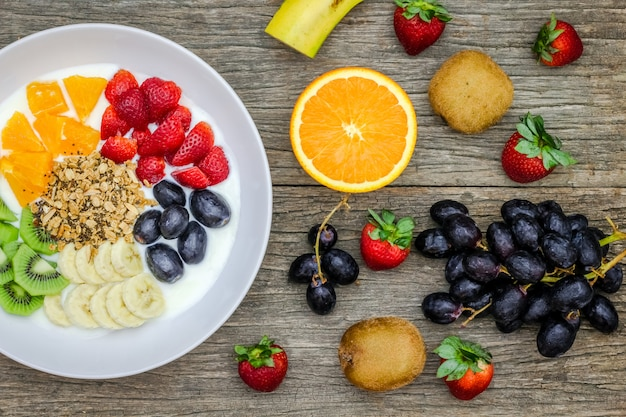 Plaat van natuurlijke witte yoghurt met muesli, sinaasappel, banaan, kiwi, aardbeien en druivenvruchten op houten lijst