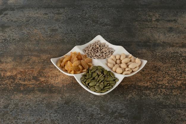 Plaat van noten, zaden op marmeren tafel.