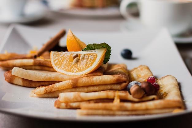 Plaat van pannekoeken, noten en bosbessen, sinaasappelenstukken. stuk maslenitsa boterweek festivalmaaltijd. vastenavond. pannenkoeken dag.