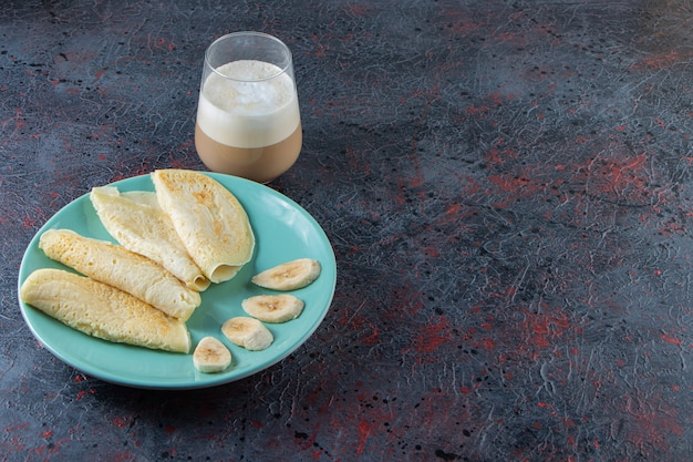 Plaat van pannenkoeken en gesneden bananen met glas melkkoffie op donkere ondergrond.