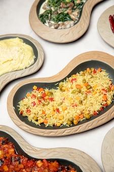 Plaat van pilaf bereid met maïs en groene erwten
