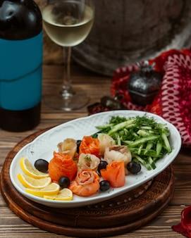 Plaat van plakjes zalm en tonijn gerold in bloemvorm met citroen