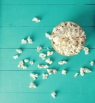 Plaat van popcorn op een blauwe houten achtergrond, bovenaanzicht