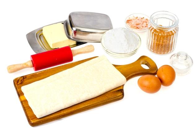 Plaat van rauw zelfgemaakt bakseldeeg op witte tafel.