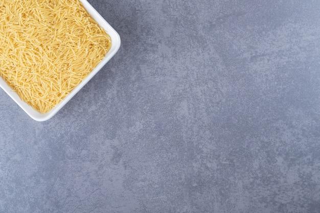 Plaat van rauwe macaroni op stenen achtergrond.