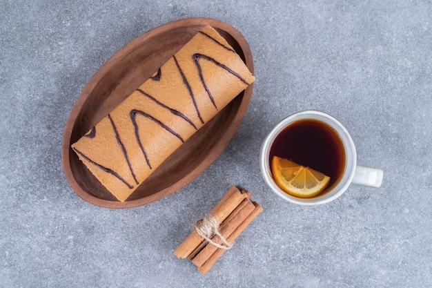 Plaat van roll cake, kopje thee en kaneelstokjes op marmeren oppervlak