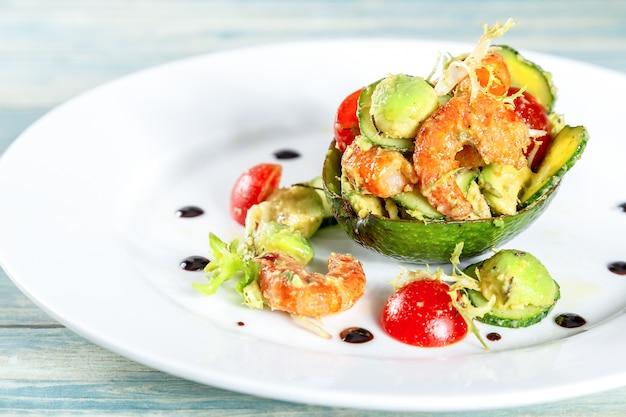 Plaat van salade met garnalen, avocado en tomaten