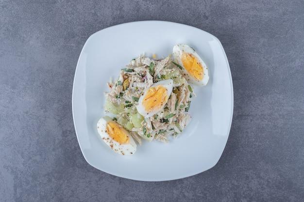 Plaat van salade met gekookt ei op stenen tafel.