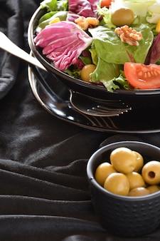 Plaat van salade met sla, tomaat, olijven en olie. op een zwarte doek