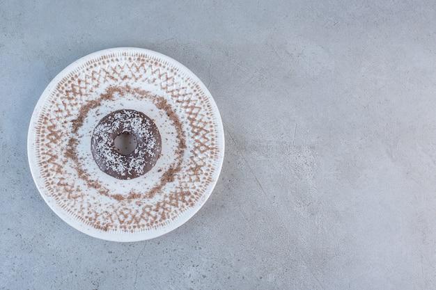 Plaat van smakelijke enkele chocolade donut op steen.