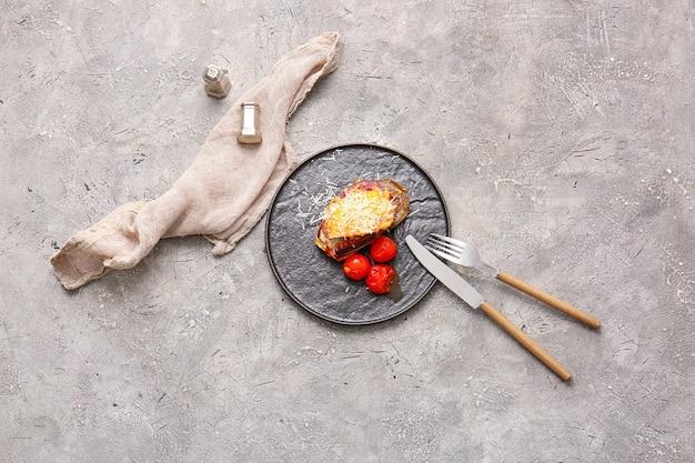Plaat van smakelijke gebakken aubergine met kaas en tomaten op grungeachtergrond