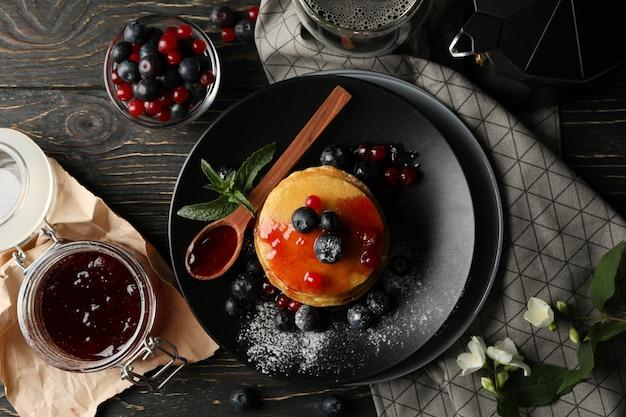 Plaat van smakelijke pannenkoeken met bessen en poeder op houten tafel. samenstelling van zoet ontbijt
