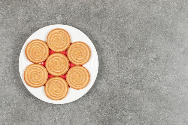 Plaat van smakelijke ronde koekjes op marmeren oppervlak