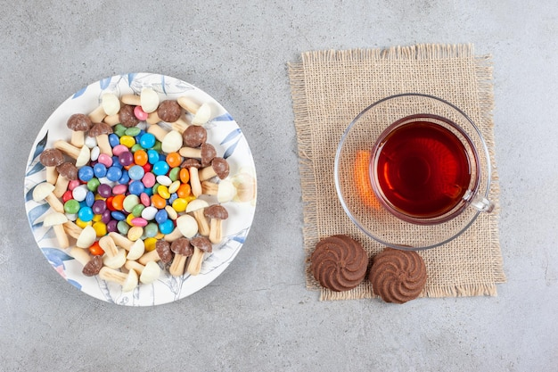 Plaat van snoepjes en chocoladepaddestoelen naast een kopje thee en twee koekjes op marmeren oppervlak