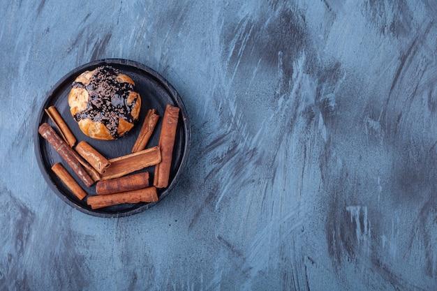 Plaat van soesjes en pijpjes kaneel en glas thee op blauw.