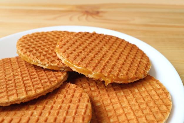 Plaat van stroopwafel-koekjes, smakelijke nederlandse traditionele snoepjes geserveerd op houten tafel