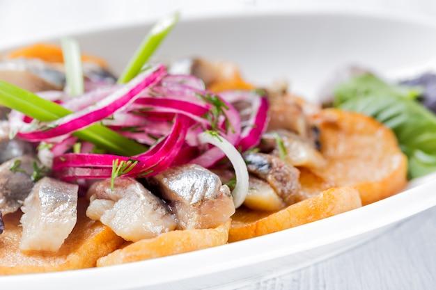 Plaat van stukjes haring met gebakken aardappel, ui en salade