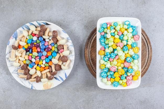 Plaat van suikergoed en chocoladepaddestoelen naast een plaat van popcornsuikergoed op een houten dienblad op marmeren oppervlakte