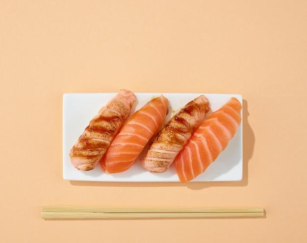 Plaat van sushi op pastelkleurige achtergrond, bovenaanzicht