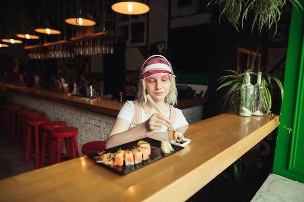Plaat van sushi rolt in restaurant met eetstokjes van de vrouwenholding