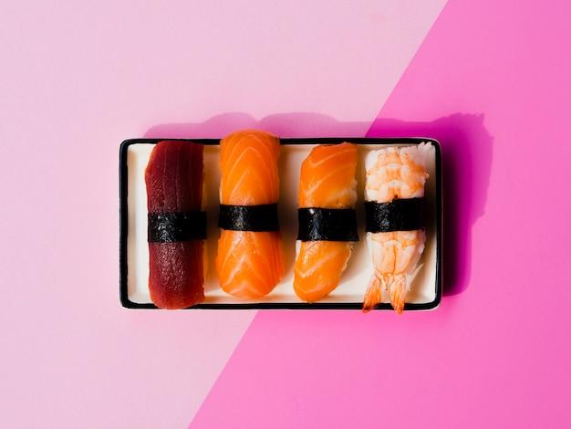Plaat van sushi variaton op een roze achtergrond