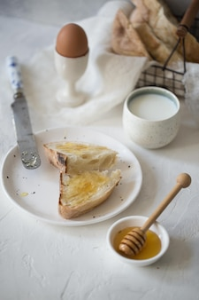 Plaat van toast met honing ei melk ontbijt foto van hoge kwaliteit