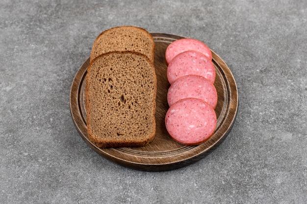 Plaat van toast met salami op stenen tafel.