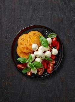 Plaat van tomaat en mozzarella salade op zwarte houten keukentafel, bovenaanzicht