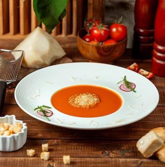 Plaat van tomatensoep gegarneerd met geraspte parmezaanse kaas in soepkom