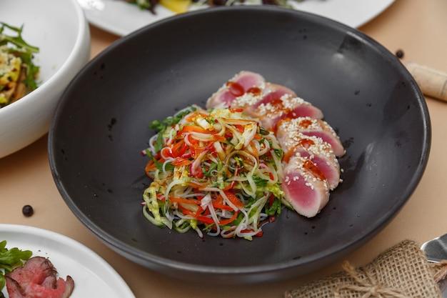 Plaat van tonijnsteak met salade beige tafel
